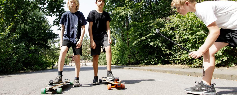 Jungen mit Skateboards werden mit einer Action Cam gefilmt.