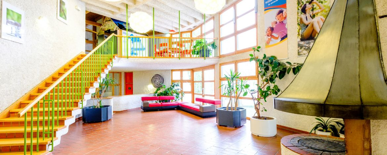 Lobby in der Jugendherberge mit Kamin und Sitzmöglichkeiten