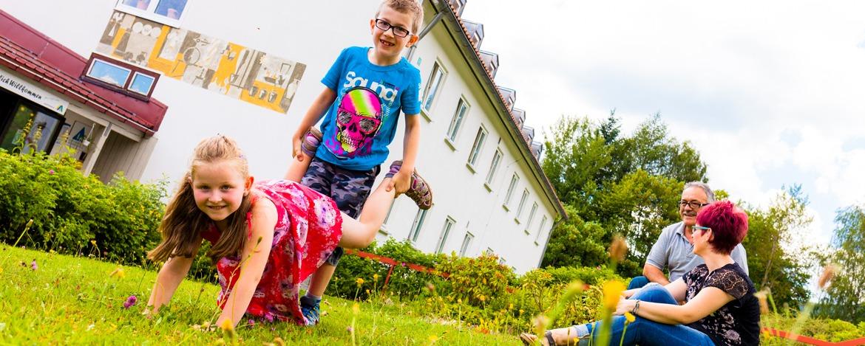 Kinder spielen auf der Wiese hinter der Jugendherberge Bayerisch Eisenstein