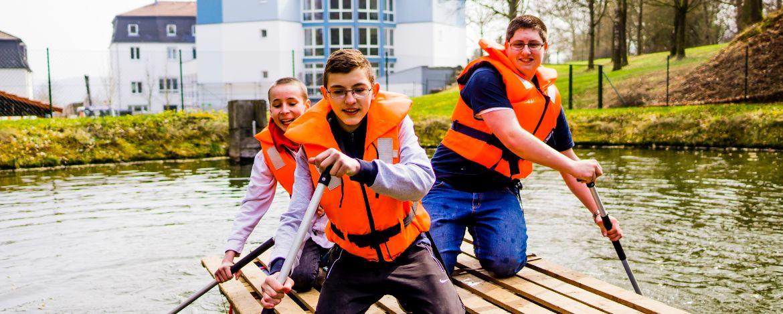 Jungen auf einem selbstgebauten Floß - Klassenfahrt mit Floßbau