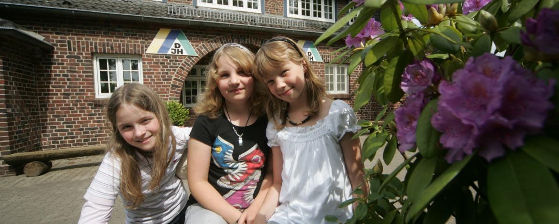 Hausansicht mit Blumen und Kids