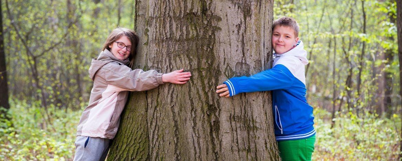 Kinder umarmen einen Baumstamm