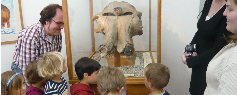 Kinder vor einem Mammutkopf
