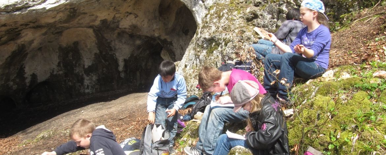 Kinder vor einer Höhle